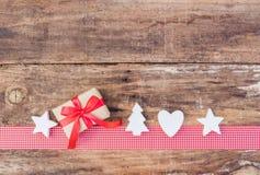 圣诞节与礼物和装饰品的贺卡装饰在红色丝带边界和木头背景 免版税图库摄影