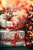 圣诞节与礼物盒、红色装饰球和鸟的贺卡在欢乐bokeh照明设备背景,垂直 库存图片