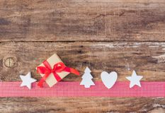 圣诞节与礼物盒和装饰品的贺卡装饰在红色丝带边界和木头背景 库存照片
