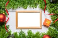 圣诞节与空白的框架的杉树在一张木桌上 免版税库存照片