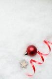 圣诞节与红色中看不中用的物品、丝带漩涡和星的雪背景 免版税库存图片