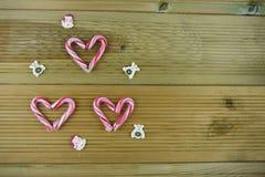 圣诞节与红色和白色条纹棒棒糖甜点的摄影图象在爱心脏塑造与在木头的逗人喜爱的被冰的装饰 图库摄影