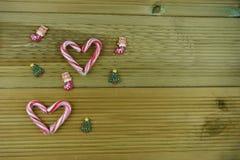 圣诞节与红色和白色条纹棒棒糖甜点的摄影图象在爱心脏塑造与在木头的逗人喜爱的被冰的装饰 库存图片