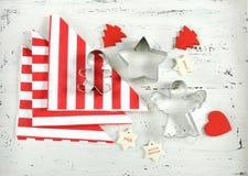 圣诞节与红色和白色题材曲奇饼切削刀的假日背景在白色木头 免版税库存图片