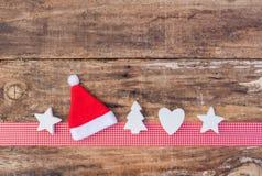 圣诞节与红色圣诞老人帽子和装饰品的贺卡装饰在红色丝带边界和木头背景 免版税库存图片