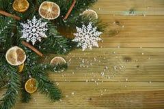 圣诞节与绿色树枝的摄影图象留给桂香橙色切片和白色雪花装饰雪 库存照片