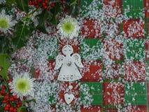 圣诞节与花和天使的树装饰的摄影与霍莉和红色莓果的图象和心脏洒与雪 免版税库存照片