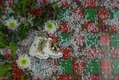 圣诞节与花和滑冰的起动的树装饰的摄影图象与霍莉和红色莓果的洒与雪 免版税库存照片