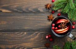 圣诞节与苹果计算机和蔓越桔的被仔细考虑的酒 用冷杉分支、蔓越桔和香料装饰的假日概念 免版税库存照片