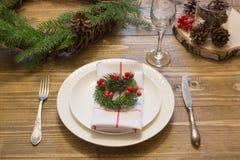 圣诞节与葡萄酒餐具、银器和装饰的餐位餐具在木板 作为装饰的圣诞节花圈 库存图片