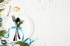圣诞节与蓝色和金黄装饰和常青树的桌设置 免版税库存图片