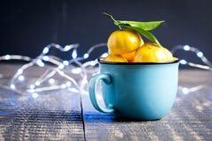 圣诞节与蜜桔木背景假日装饰的新年构成到俄国传统杯柑橘拷贝空间 库存图片