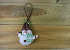 圣诞节与逗人喜爱的愉快的白色软的物质雪人的摄影图象在绿色雪花样式围巾和帽子在自然木头 免版税图库摄影