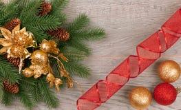 圣诞节与锥体的云杉分支在与黄色和红色球的黑暗的背景 免版税库存照片