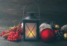 圣诞节与锥体的灯和玻璃球形在木背景 免版税图库摄影