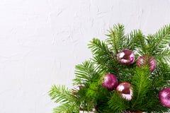 圣诞节与闪烁洋红色和桃红色中看不中用的物品, c的贺卡 免版税库存图片