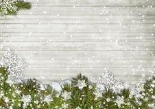 圣诞节与降雪的杉树在一个木板 免版税图库摄影