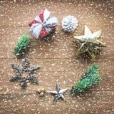 圣诞节与降雪的装饰品装饰在木头 免版税库存图片