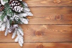 圣诞节与雪的杉树在土气木板 免版税图库摄影