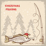 圣诞节与鱼的渔卡片在红色圣诞老人帽子。 免版税库存照片