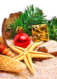 圣诞节中看不中用的物品、海星、礼物盒和杉木枝杈在沙子 免版税库存图片