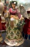 圣诞节举与某一欢乐Bokeh的玩具天使一个蜡烛在前景 图库摄影