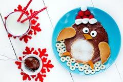 圣诞节乐趣孩子的食物想法-企鹅薄煎饼 免版税库存图片