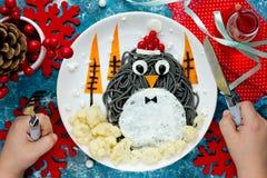 圣诞节乐趣食物孩子的艺术想法-企鹅黑spagehetti 免版税库存图片