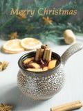 圣诞节仔细考虑了酒用桂香、桔子和茴香在一个陶瓷桶 题字圣诞快乐 库存图片