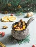 圣诞节仔细考虑了酒用桂香、桔子和茴香在一个陶瓷桶 免版税库存照片