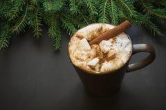 圣诞节传统饮料 在黑色的热巧克力用蛋白软糖和桂香与圣诞树分支 图库摄影