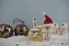 圣诞节使用作为雪人和身分被塑造的蛋白软糖的食物摄影在雪与奶油色海绵神仙的蛋糕和中看不中用的物品 图库摄影