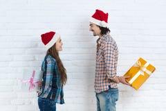 圣诞节假日愉快的夫妇举行惊奇礼物箱子面带新年圣诞老人帽子盖帽、男人和妇女微笑 免版税库存图片