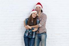 圣诞节假日愉快的夫妇佩带新年圣诞老人帽子盖帽、男人和妇女爱微笑拥抱 免版税库存图片