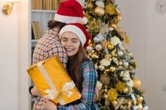 圣诞节假日愉快的夫妇佩带新年圣诞老人拥抱在装饰的树附近的帽子盖帽、男人和妇女拿着礼物 免版税图库摄影