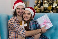 圣诞节假日愉快的夫妇佩带新年圣诞老人拥抱帽子盖帽、的男人和的妇女拿着当前箱子 免版税图库摄影