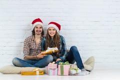 圣诞节假日愉快的夫妇坐地板穿戴新年圣诞老人微笑与当前箱子的帽子盖帽、男人和妇女 免版税库存照片
