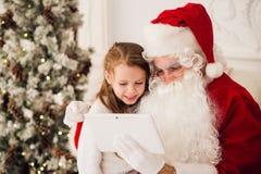 圣诞节假日愉快的女孩看某事在数字式触摸屏片剂个人计算机的圣诞老人,在烟囱和树 图库摄影