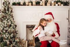圣诞节假日愉快的女孩看某事在数字式触摸屏片剂个人计算机的圣诞老人,在烟囱和树 免版税库存照片