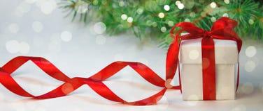 圣诞节假日构成 在白色箱子的新年礼物有在轻的背景的红色丝带的与杉树 复制空间 库存照片