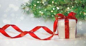 圣诞节假日构成 在白色箱子的新年礼物有在轻的背景的红色丝带的与杉树 复制空间 免版税库存照片