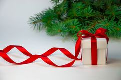 圣诞节假日构成 在白色箱子的新年礼物有在轻的背景的红色丝带的与杉树 复制空间 免版税库存图片