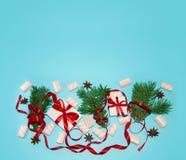 圣诞节假日构成 在白色箱子的新年礼物用红色丝带杉树分支八角蛋白软糖 免版税库存图片