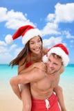 圣诞节假期海滩乐趣夫妇肩扛 免版税图库摄影