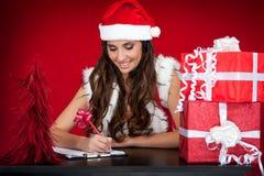 圣诞节做当前圣诞老人愿望的女孩列&# 免版税图库摄影