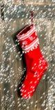 圣诞节储存 与雪花和落的雪的红色袜子 免版税库存照片