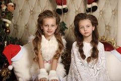 圣诞节内部的两个女孩姐妹 库存照片