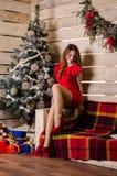 圣诞节内部的美丽的妇女庆祝愉快在背景 库存图片