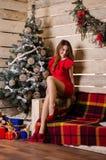 圣诞节内部的美丽的妇女庆祝愉快在背景 免版税图库摄影