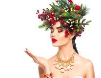 圣诞节冬天吹与在她的不可思议的雪的时尚女孩移交白色 免版税库存照片